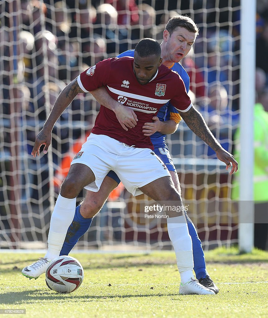 Emile Sinclair of Northampton Town attempts to control the ball under pressure from John Dempster of Mansfield Town during the Sky Bet League Two match between Northampton Town and Mansfield Town at Sixfields on March 15, 2014 in Northampton, England.