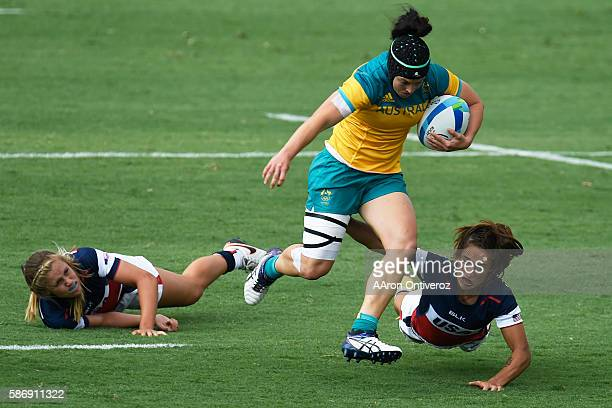 Emilee Cherry of Australia evades tackle attempts by Richelle Stephens and Ryan Carlyle of the United States during their 1212 rugby sevens tie at...