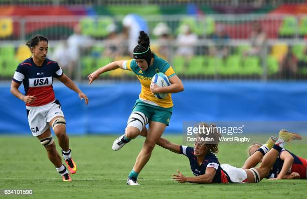 Emilee Cherry of Australia makes a break past Ryan Carlyle of the United States during the Women's Rugby Sevens Pool A match between Australia and...
