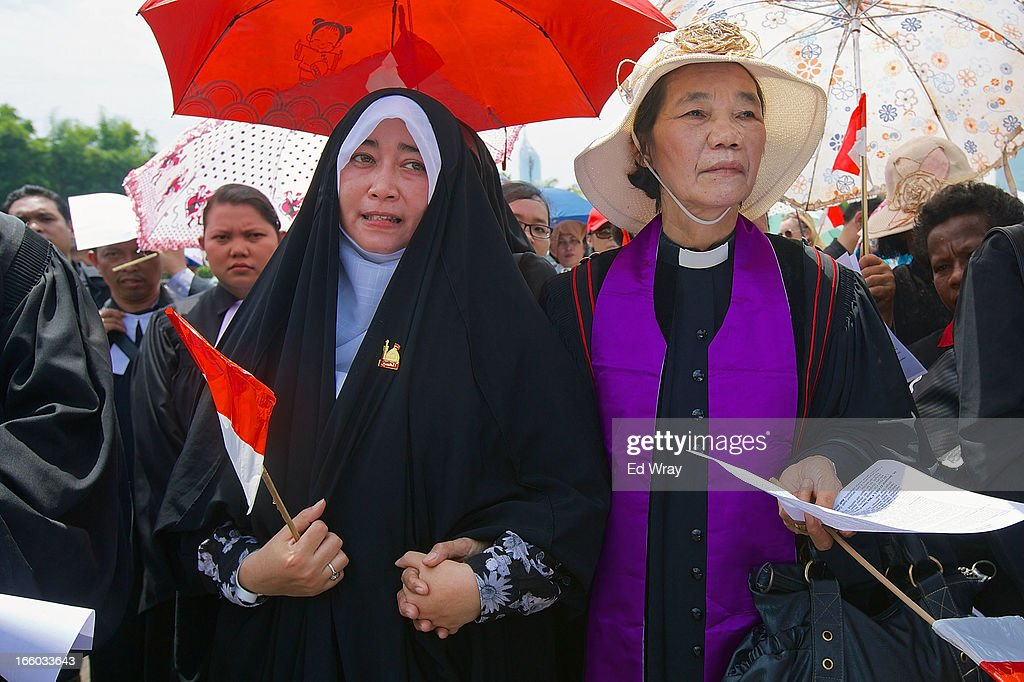 Emilia Az, a member of the Shia community and Anna Menoharan, a Christian pastor hold hands in front of the Indonesian parliament as Clergy and leaders from Christian and Muslim religious minority groups marched to the parliament to demonstrate for religious tolerance on the streets of Jakarta on April 8, 2013 in Jakarta, Indonesia. Recent reports suggest upwards of 260 violent attacks against religious minorities occured in 2012 in Indonesia.