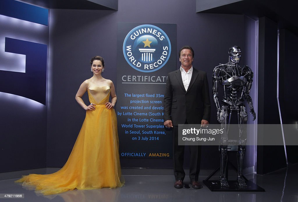 Emilia Clarke and Arnold Schwarzenegger pose in front of the sign a listed in the Guinness book of records as largest theater screen in the world...