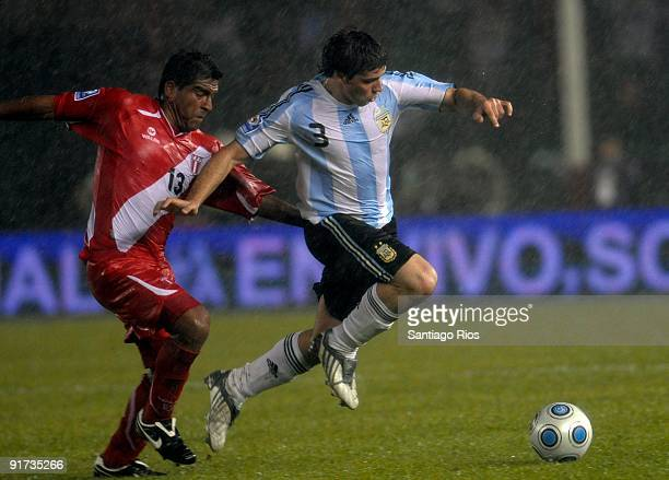 Emiliano Insua of Argentina vies for the ball with Christian Ramos of Peru during their match as part of the FIFA 2010 World Cup Qualifier at...