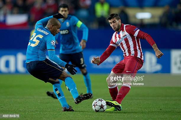 Emiliano Insua of Atletico de Madrid competes for the ball with Fernando Reges of FC Porto during the UEFA Champions League Group G match at Vicente...
