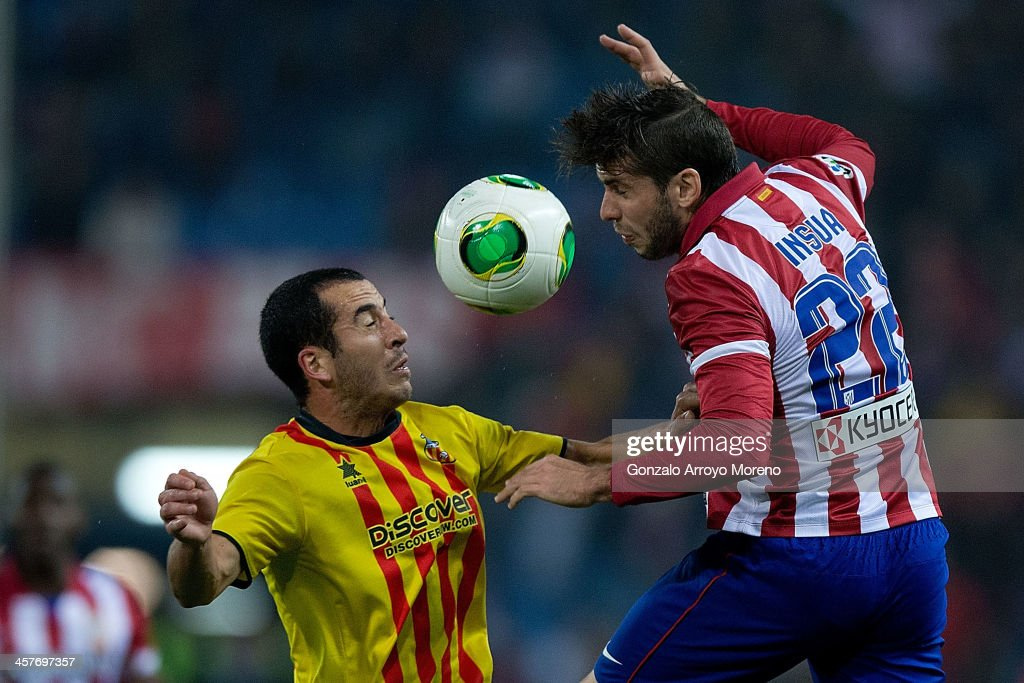 <a gi-track='captionPersonalityLinkClicked' href=/galleries/search?phrase=Emiliano+Insua&family=editorial&specificpeople=4125596 ng-click='$event.stopPropagation()'>Emiliano Insua</a> (R) of Atletico de Madrid competes for the ball with Xapi Arnau (L) of UE Sant Andreu during the Copa del Rey Round of 32 second leg match between Club Atletico de Madrid and Sant Andreu at Vivente Calderon Stadium on December 18, 2013 in Madrid, Spain.