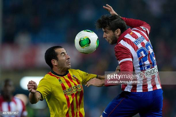 Emiliano Insua of Atletico de Madrid competes for the ball with Xapi Arnau of UE Sant Andreu during the Copa del Rey Round of 32 second leg match...