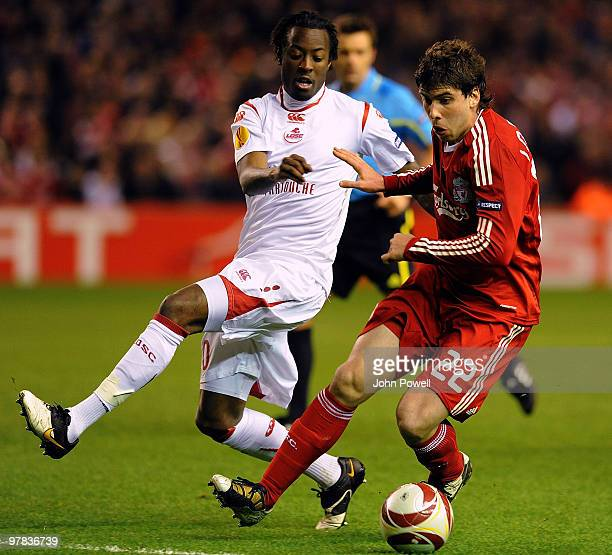 Emiliano Insua of Liverpool competes with Larsen Toure of Lille during the UEFA Europa League Round of 16 second leg match between Liverpool and...