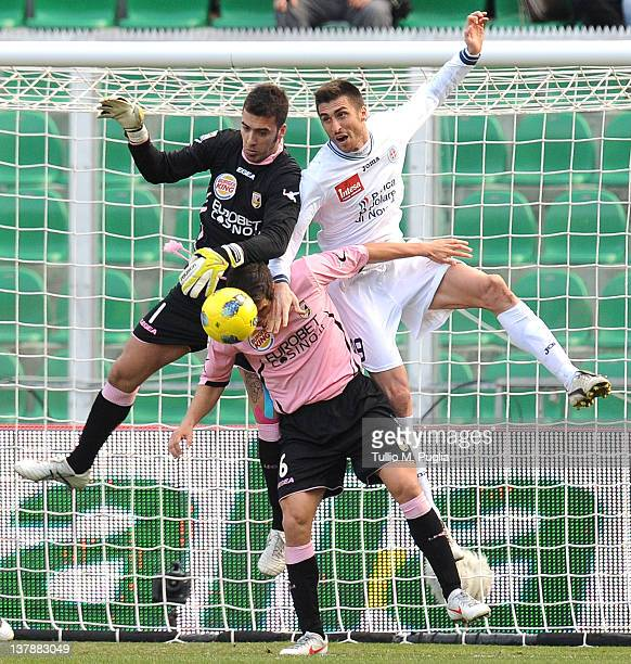 Emiliano Viviano goalkeeper of Palermo and Andrea Caracciolo of Novara jump for the ball as Ezequiel Munoz of Palermo reacts during the Serie A match...