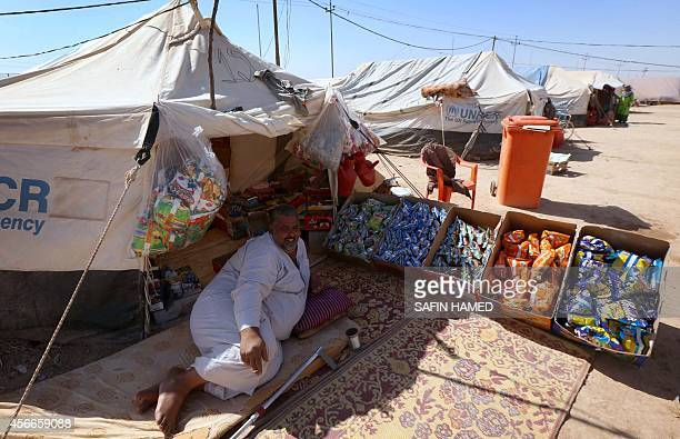 Emilienne Malfatto A displaced Iraqi who had fled his home after an offensive led by the Islamic State jihadist group sells food at his tent provided...