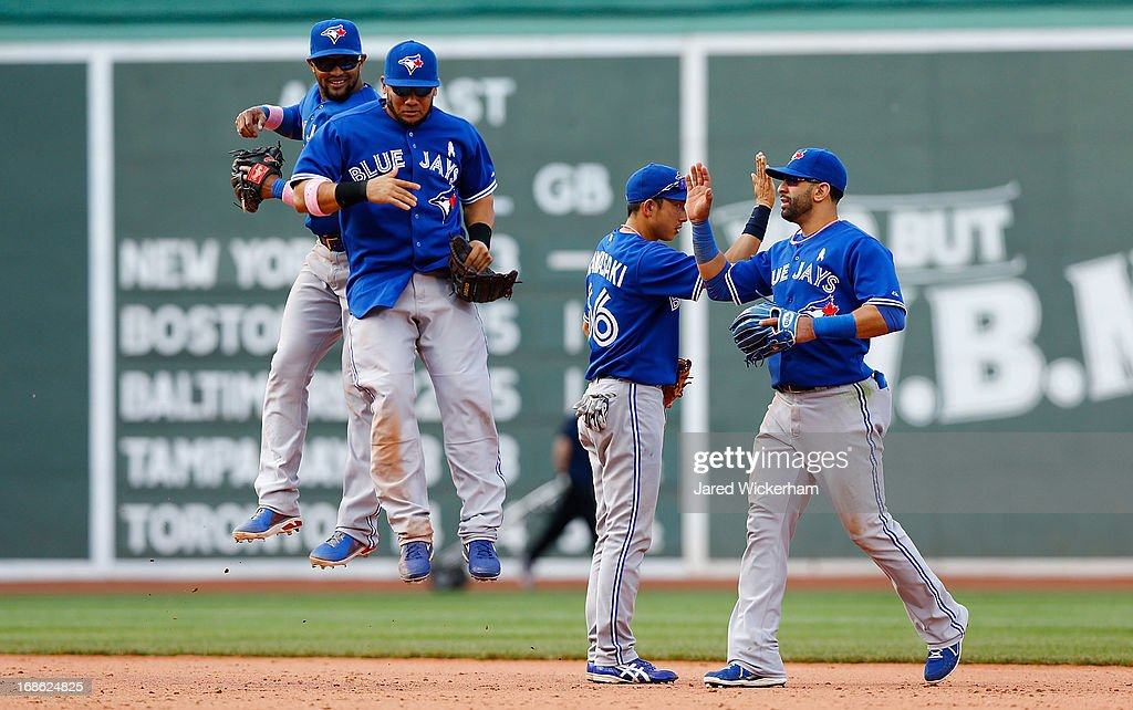 Emilio Bonifacio, Melky Cabrera #53, Munenori Kawasaki #66, and Jose Bautista #19 of the Toronto Blue Jays celebrate following their 12-4 win against the Boston Red Sox during the game on May 12, 2013 at Fenway Park in Boston, Massachusetts.