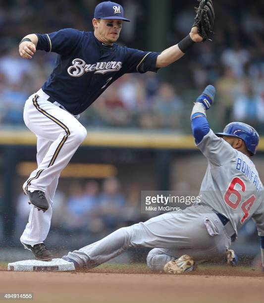 Emilio Bonifacio of the Chicago Cubs beats the throw to Scooter Gennett of the Milwaukee Brewers during the top of the fourth inning against the...