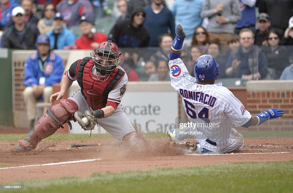 <a gi-track='captionPersonalityLinkClicked' href=/galleries/search?phrase=Emilio+Bonifacio&family=editorial&specificpeople=4193706 ng-click='$event.stopPropagation()'>Emilio Bonifacio</a> #64 of the Chicago Cubs scores past catcher <a gi-track='captionPersonalityLinkClicked' href=/galleries/search?phrase=Miguel+Montero&family=editorial&specificpeople=836495 ng-click='$event.stopPropagation()'>Miguel Montero</a> #26 of the Arizona Diamondbacks on a ball hit by Anthony Rizzo #44 during the first inning at Wrigley Field on April 24, 2014 in Chicago, Illinois. Left fielder Roger Kieschnick #22 made a fielding error on Rizzo's fly ball allowing Bonifacio to score.