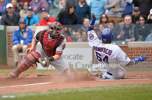 Emilio Bonifacio of the Chicago Cubs scores past catcher Miguel Montero of the Arizona Diamondbacks on a ball hit by Anthony Rizzo during the first...