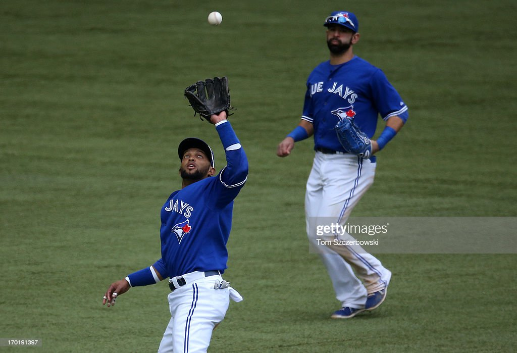 Emilio Bonifacio #1 of the Toronto Blue Jays catches a pop up in the sixteenth inning as Jose Bautista #19 watches during MLB game action against the Texas Rangers on June 8, 2013 at Rogers Centre in Toronto, Ontario, Canada.
