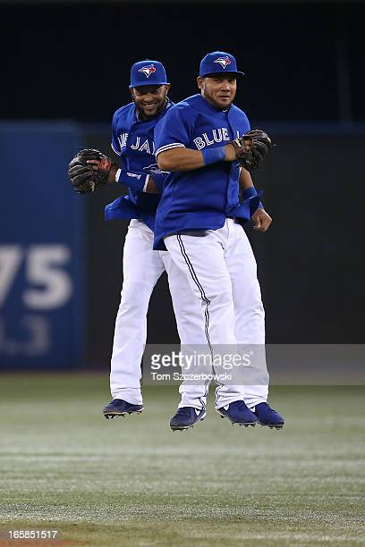 Emilio Bonifacio of the Toronto Blue Jays celebrates with Melky Cabrera during MLB game action after defeating the Boston Red Sox on April 6 2013 at...