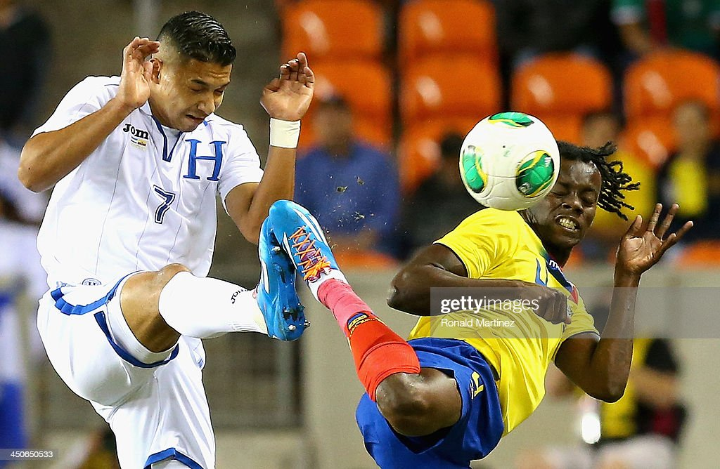 Emilio Izaguirre of Honduras jumps for the ball against Juan Carlos Paredes of Ecuador during an international friendly match at BBVA Compass Stadium on November 19, 2013 in Houston, Texas.