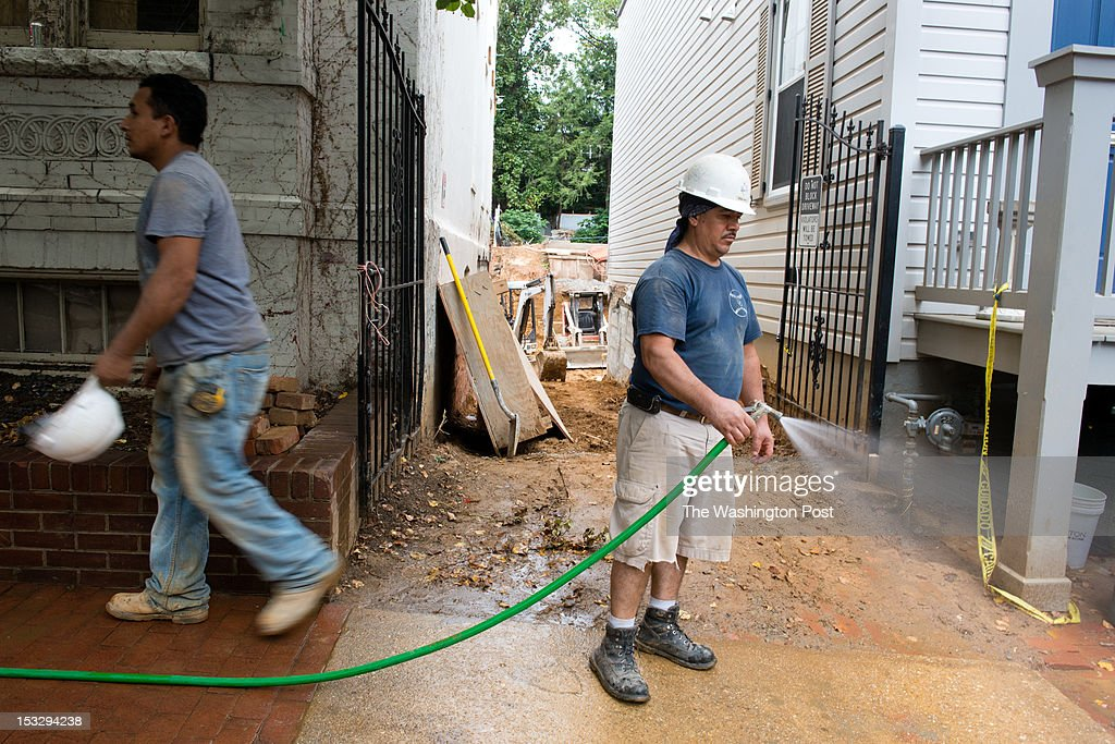 Emilio Lopez, right of CBD Construction, sprays mud from the front sidewalk. African-American human remains that are believed to be pre-Civil War were discovered on September 10th in the 3000 block of Q St. NW while construction was taking place in the rear of the home. Since then, three other sets of remains have been discovered at the site.