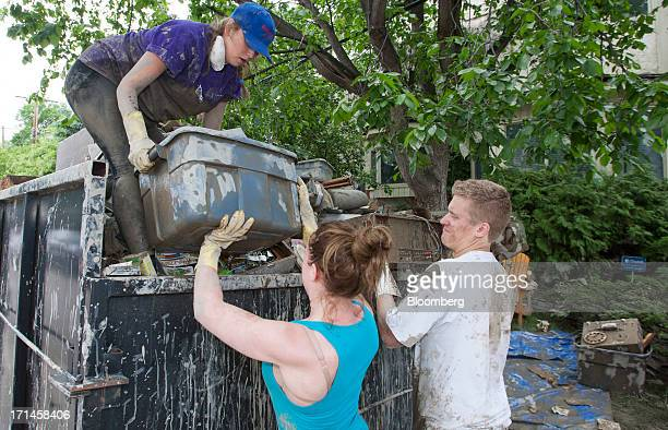 Emily Ebbels left Kyli Lane center and Charlie Hogarth help a friend's family clean up in Rideau Park after flooding in Calgary Alberta Canada on...