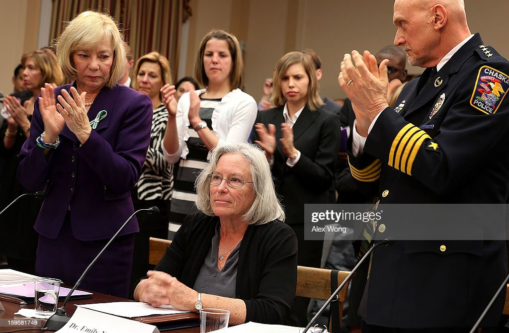 Emily Nottingham (C), mother of Gabe Zimmerman, a staff member to former Rep. Gabrielle Giffords' who was killed during the Tucson, Arizona shootings receives a standing ovation, including from Superintendent of schools of Newtown, Connecticut, Janet Robinson (L) and chief of police for the City of Chaska, Minnesota, Scott Knight (R) during a hearing before the House Democratic Steering and Policy Committee January 16, 2013 on Capitol Hill in Washington, DC. The committee held a hearing to focus on 'Gun Violence Prevention: A Call to Action.'