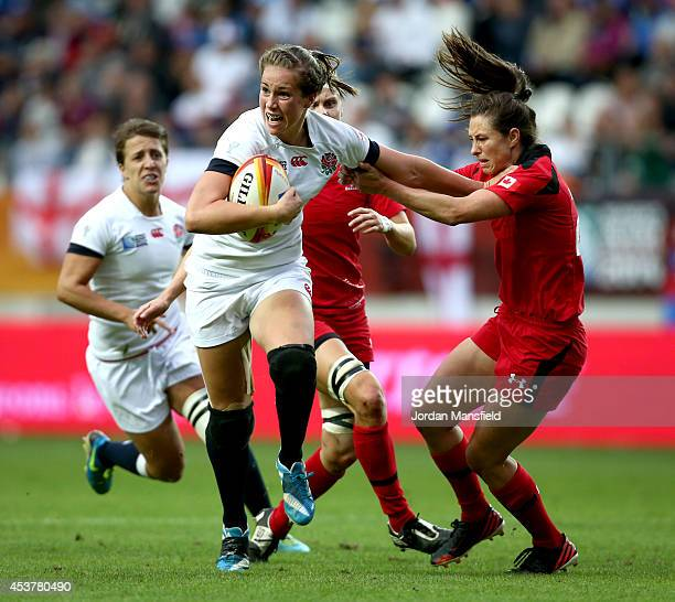 Emily Scarratt of England breaks free from a tackle by Brittany Waters of Canada during the IRB Women's Rugby World Cup 2014 Final between England...