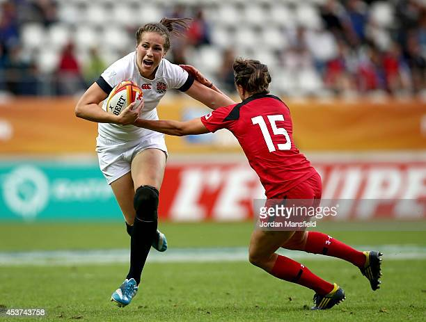 Emily Scarratt of England is tackled by Julianne Zussman of Canada during the IRB Women's Rugby World Cup 2014 Final between England and Canada at...