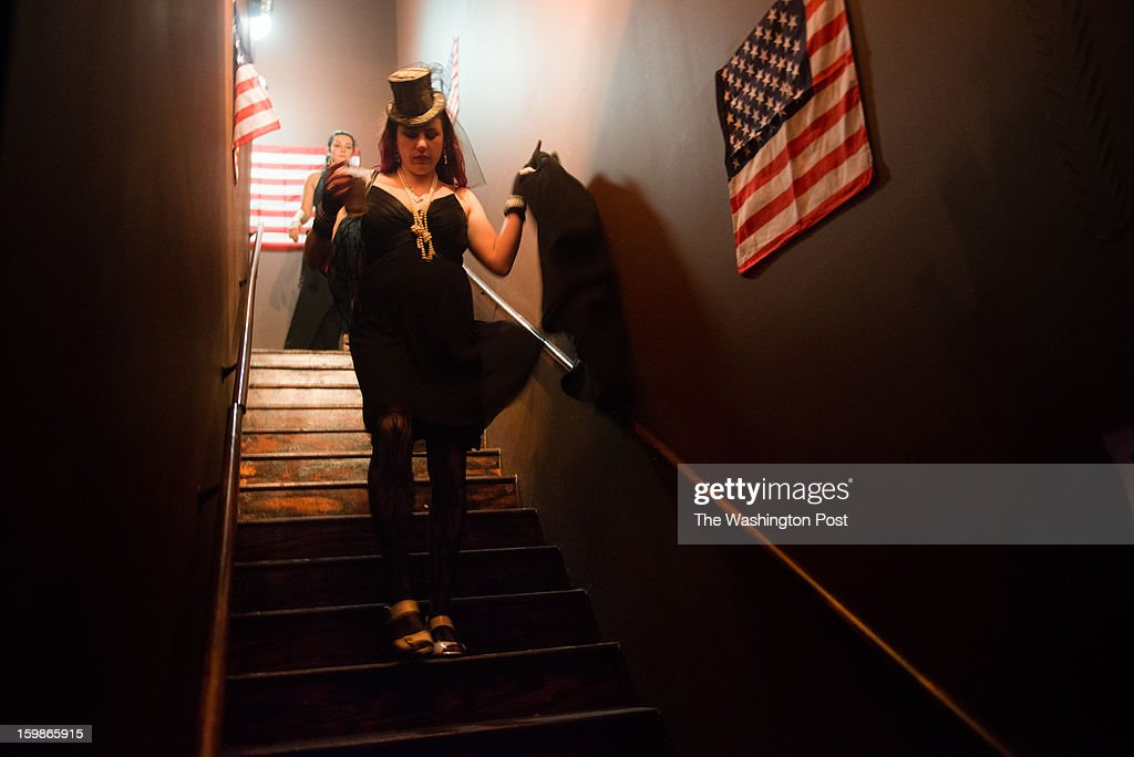 Emily Todd, 28, of Arlington walks down the stairs past American Flags. She was volunteering at the event. The 2013 Artist's Inaugural Ball featured live music, fire performances, Djs, dancing, a hookah lounge and more. It was spread among six areas in the Rock and Roll Hotel and Gallery O on H. A portion of the proceeds went to local charities, Miriam's Kitchen and One Common Unity. The hosts were Mischief, Rogue Wave Project, Artomatic, and Meso Creso.
