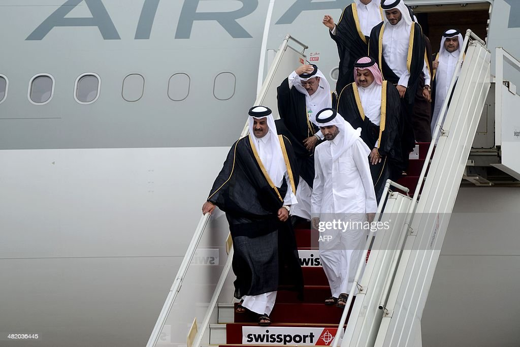 Emir of Qatar, Sheikh Tamim bin Hamad Al-Thani (front-L) exits the plane upon his arrival at Algiers's International Airport on April 2, 2014.