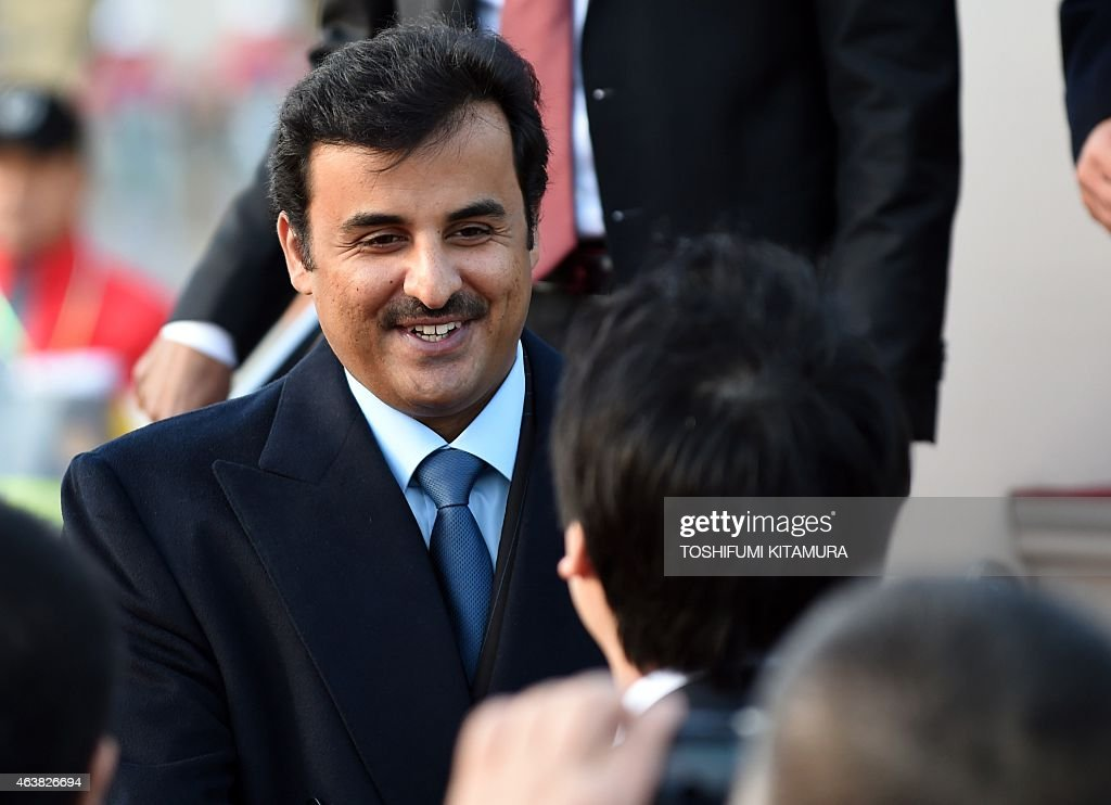Emir of Qatar, Sheikh Tamim bin Hamad Al-Thani (L) greets well-wishers upon his his arrival at the Haneda International airport in Tokyo on February 19, 2015. Emir Al Thani arrived to start his three-day visit to Japan.
