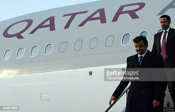 Emir of Qatar Sheikh Tamim bin Hamad AlThani walks out of the airplane upon his arrival at the Haneda International airport in Tokyo on February 19...