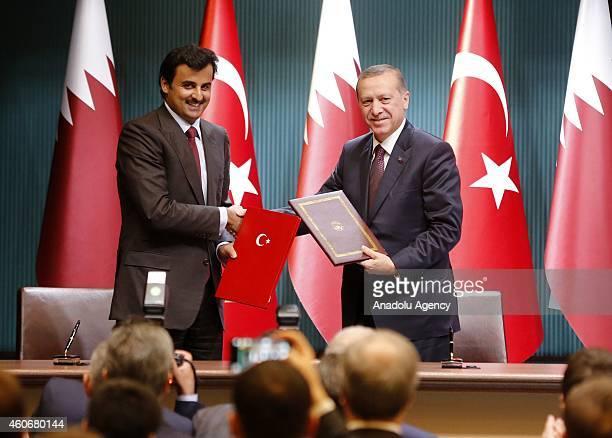 Emir of Qatar Sheikh Tamim bin Hamad bin Khalifa Al Thani and Turkish President Recep Tayyip Erdogan shake hands after they signed political...