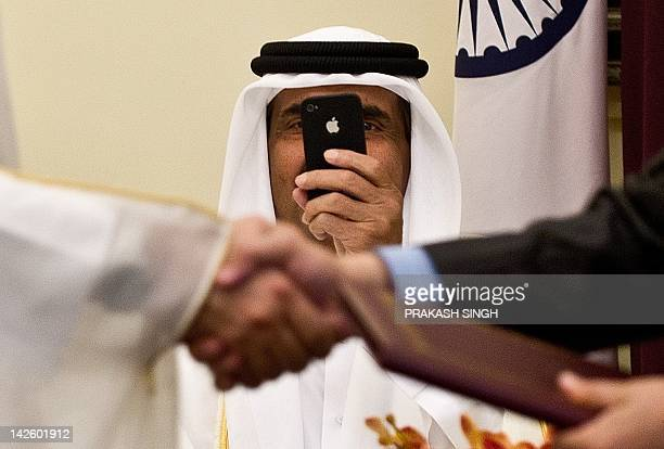 Emir of the State of Qatar Sheikh Hamad Bin Khalifa AlThani takes pictures with his Iphone as Indian Human Resource Development Minister Kapil Sibal...