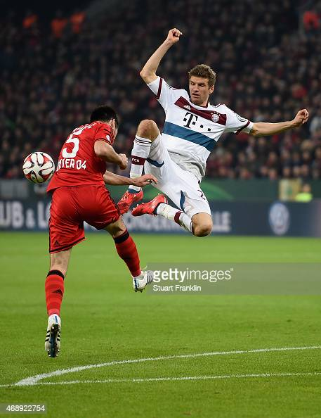 Emir Spahic of Bayer Leverkusen clears the ball under the pressure of Thomas Mueller of FC Bayern Muenchen during the DFB Cup Quarter Final match...