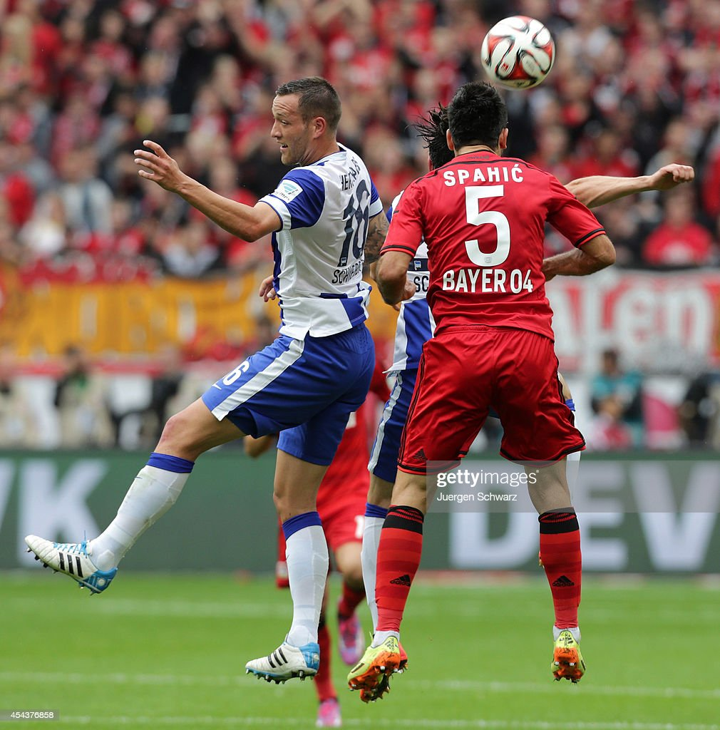 Emir Spahic of Leverkusen (#5) and <a gi-track='captionPersonalityLinkClicked' href=/galleries/search?phrase=Julian+Schieber&family=editorial&specificpeople=4272399 ng-click='$event.stopPropagation()'>Julian Schieber</a> of Berlin jump for a header during the Bundesliga match between Bayer Leverkusen and Hertha BSC Berlin at BayArena on August 30, 2014 in Leverkusen, Germany.