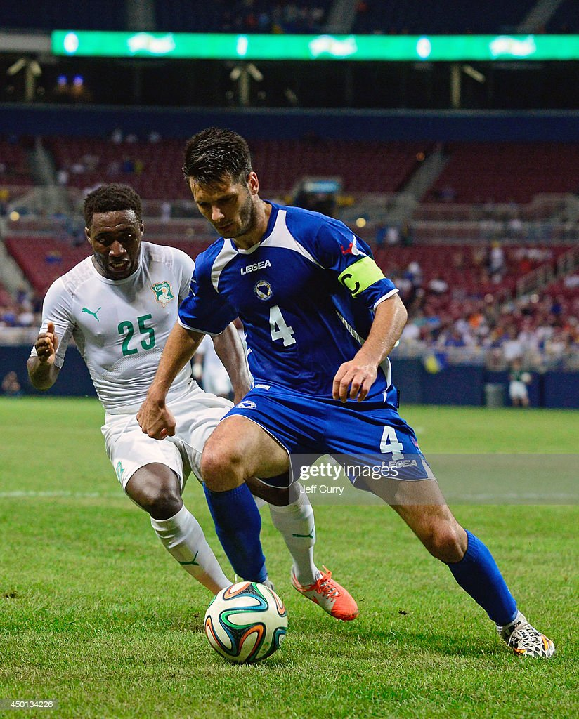 Emir Spahic #4 of the Bosnia-Herzegovina handles the ball as Brice Dja Djedje #25 of the Ivory Coast defends during the second half of a friendly match at Edward Jones Dome on May 30, 2014 in St. Louis, Missouri. Bosnia-Herzegovina defeated the Ivory Coast 2-1.