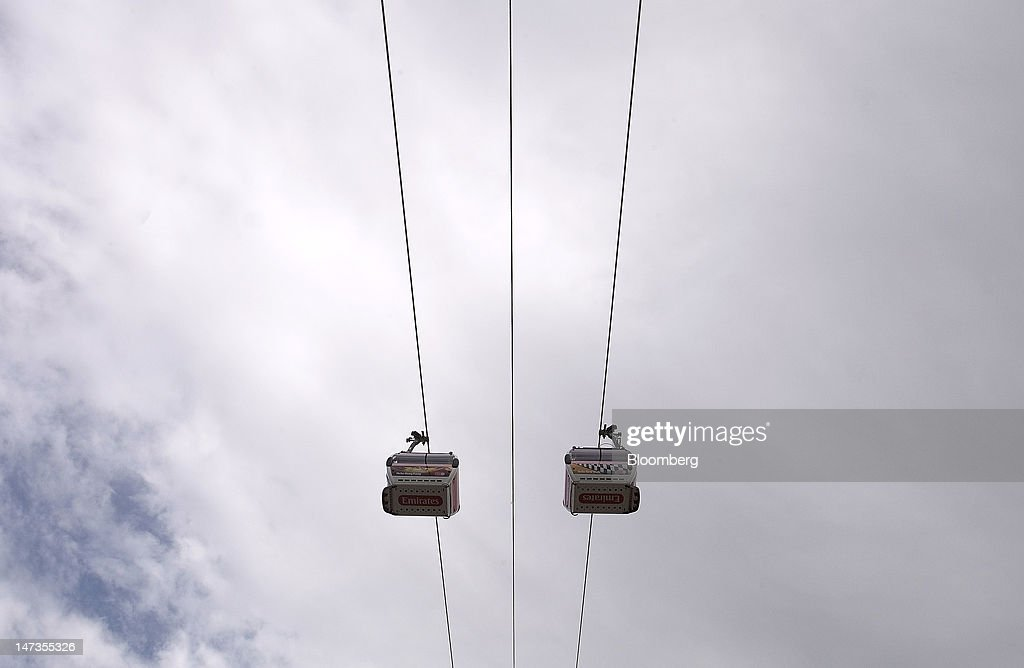 Emirates Air Line cable cars pass each other on the opening day of the new transport link crossing above the River Thames, in London, U.K., on Thursday, June 28, 2012. The cable car system, operated by Emirates, will run between Greenwich Peninsula and the Royal Victoria Docks. Photographer: Simon Dawson/Bloomberg via Getty Images