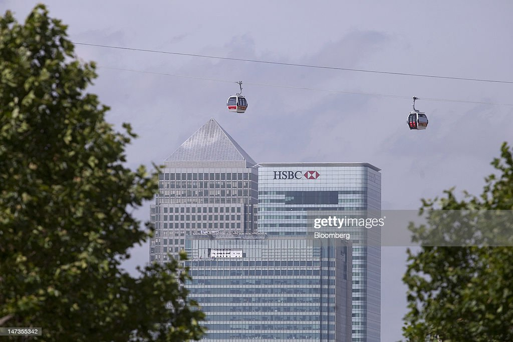 Emirates Air Line cable cars pass No. 1 Canada Square, or Canary Wharf Tower, left, Barclays Plc's headquarters, center, and the headquarters of HSBC Holdings Plc, on the opening day of the new transport link crossing above the River Thames, in London, U.K., on Thursday, June 28, 2012. The cable car system, operated by Emirates, will run between Greenwich Peninsula and the Royal Victoria Docks. Photographer: Simon Dawson/Bloomberg via Getty Images
