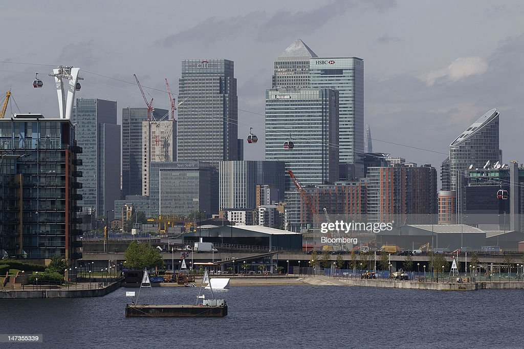 Emirates Air Line cable cars pass the Canary Wharf business and financial district, home to the offices of Barclays Plc, HSBC Holdings Plc, and Citigroup Inc., on the opening day of the new transport link crossing above the River Thames, in London, U.K., on Thursday, June 28, 2012. The cable car system, operated by Emirates, will run between Greenwich Peninsula and the Royal Victoria Docks. Photographer: Simon Dawson/Bloomberg via Getty Images