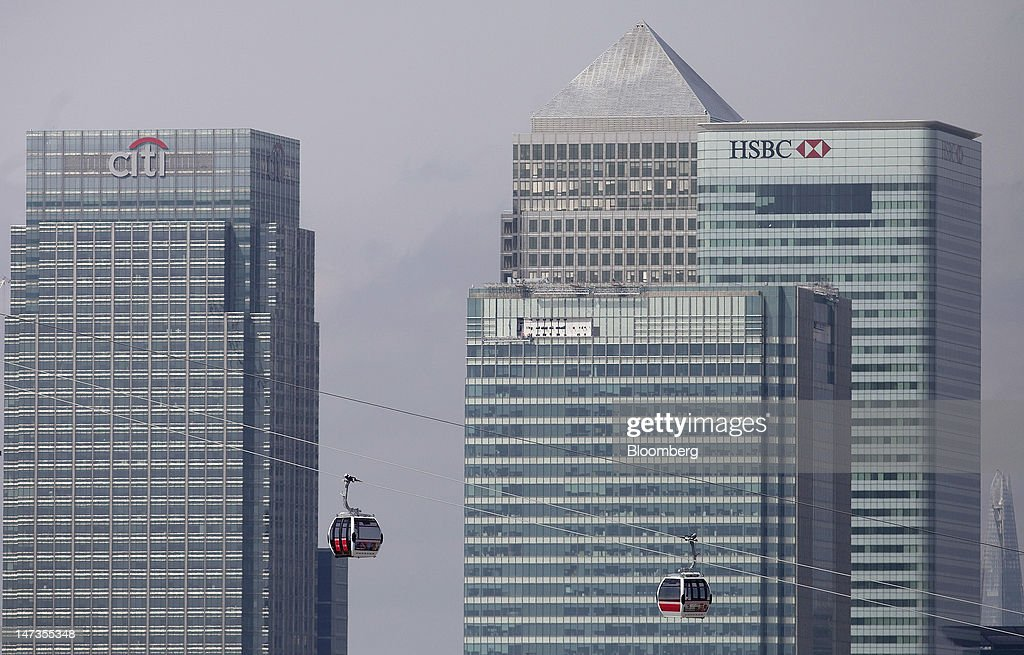 Emirates Air Line cable cars pass the offices, from left, of Citigroup Inc., Barclays Plc, No. 1 Canada Square, or Canary Wharf Tower, and HSBC Holdings Plc, on the opening day of the new transport link crossing above the River Thames, in London, U.K., on Thursday, June 28, 2012. The cable car system, operated by Emirates Airline, will run between Greenwich Peninsula and the Royal Victoria Docks. Photographer: Simon Dawson/Bloomberg via Getty Images