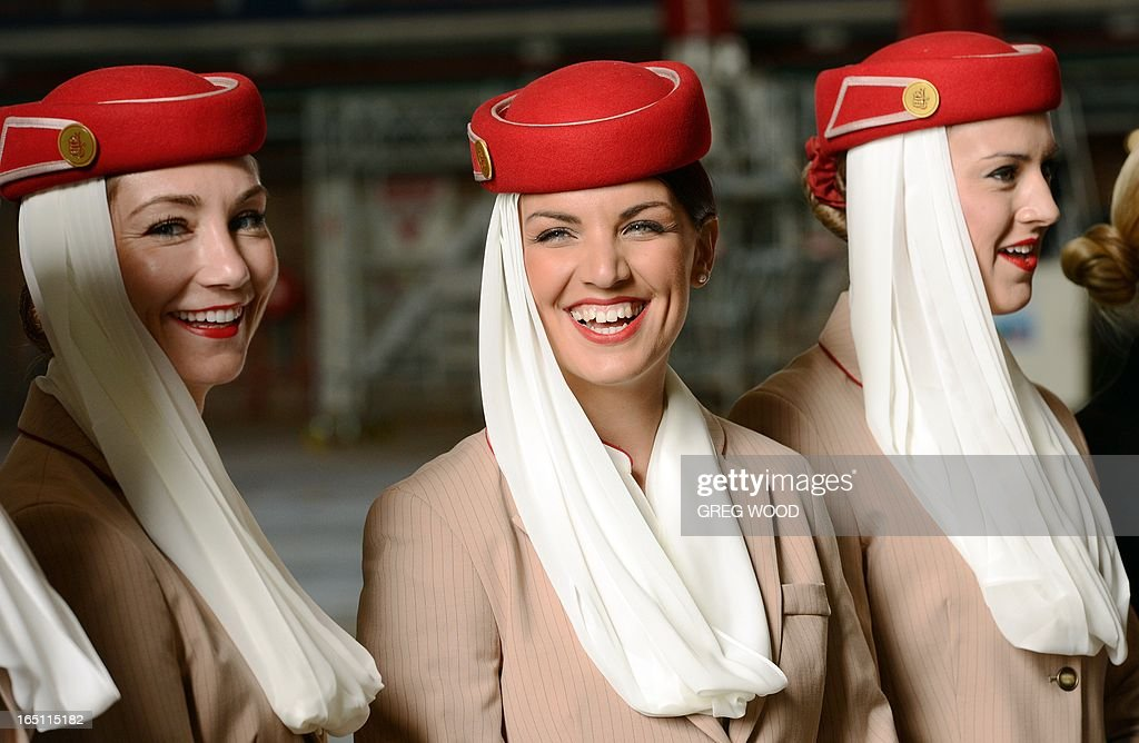 Emirates airline hostesses attend a press conference at Sydney Airport on March 31, 2013 to mark the official launch of the partnership between the Emirates and Qantas airlines. The arrangement, approved by Australia's competition watchdog on March 27, allows the carriers to combine operations for an initial period of five years, including co-ordinating ticket prices and schedules. AFP PHOTO / Greg WOOD