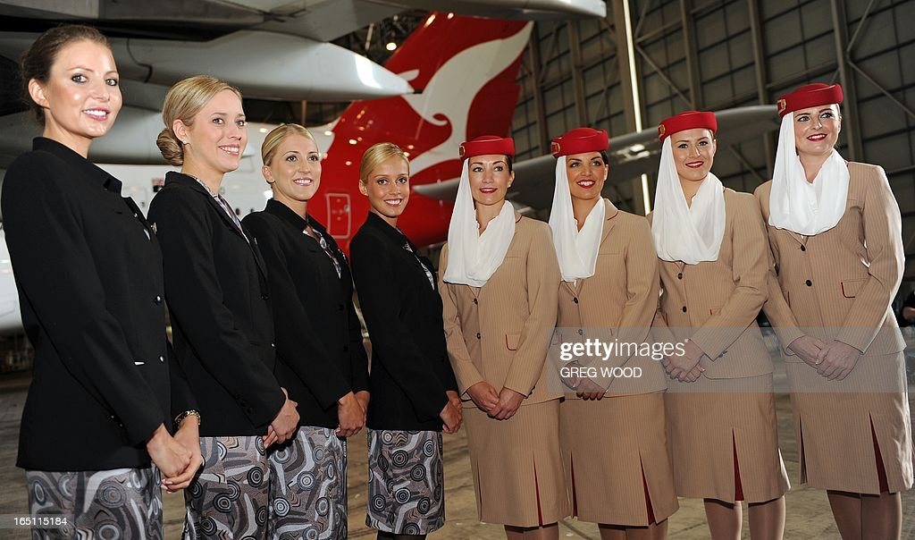 Emirates (R) and Qantas (L) airline hostesses attend a press conference at Sydney Airport on March 31, 2013 to mark the official launch of the partnership between the two carriers. The arrangement, approved by Australia's competition watchdog on March 27, allows the carriers to combine operations for an initial period of five years, including co-ordinating ticket prices and schedules. AFP PHOTO / Greg WOOD