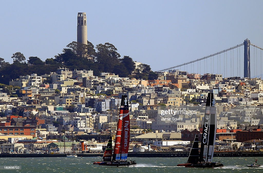 Emirates Team New Zealand and Oracle Team USA race in front of Coit Tower and the Bay Bridge during race 10 of the America's Cup finals on September 15, 2013 in San Francisco, California.