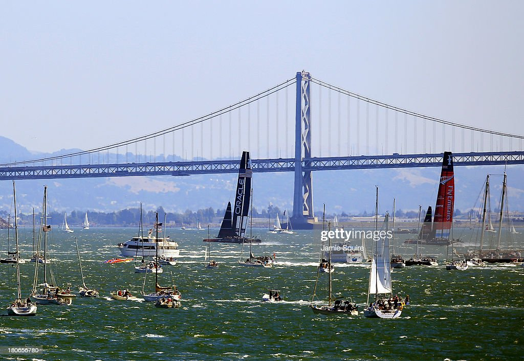 Emirates Team New Zealand and Oracle Team USA race in front of the Bay Bridge during race 10 of the America's Cup finals on September 15, 2013 in San Francisco, California.