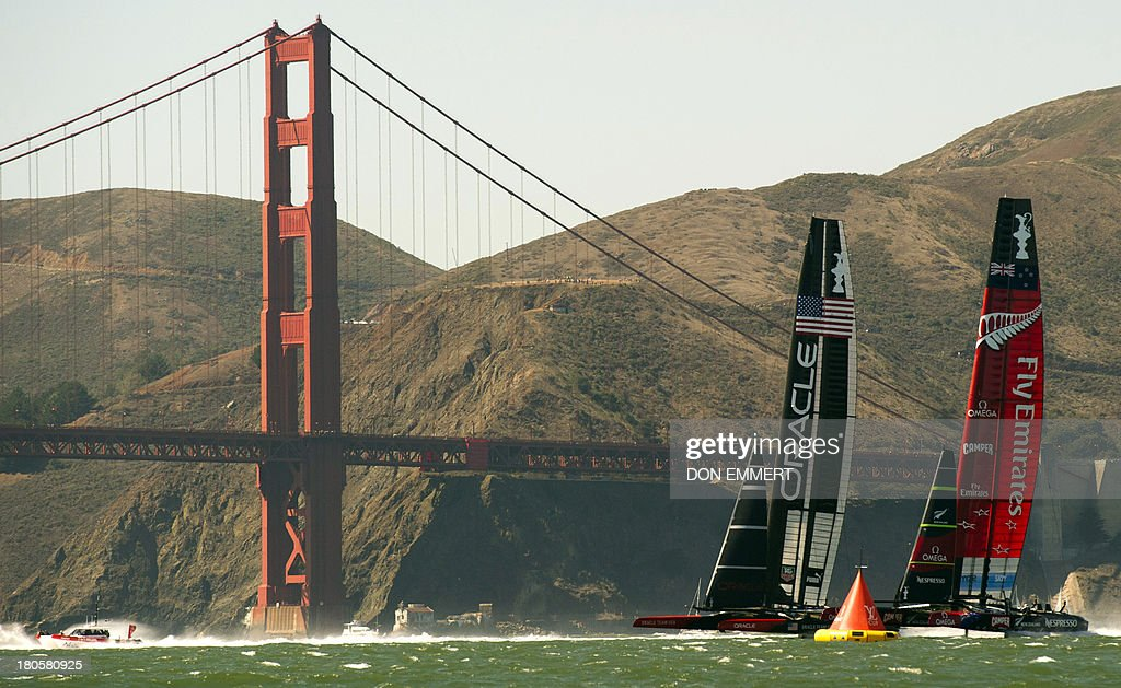 Emirates Team New Zealand (R) races against Oracle Team USA near the Golden Gate Bridge during the 34th America's Cup September 14, 2013 in San Francisco. AFP PHOTO/Don Emmert