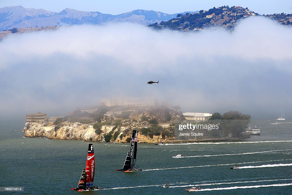 Emirates Team New Zealand races ahead of Oracle Team USA in front of Alcatraz Island partially obscured by fog during race 3 of the America's Cup...