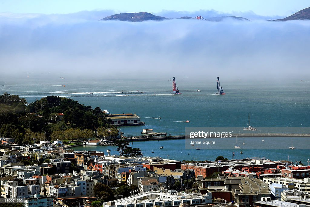 Emirates Team New Zealand races Oracle Team USA in front of the Golden Gate Bridge mostly obscured by fog during race 3 of the America's Cup finals...