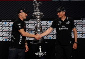 Emirates Team New Zealand skipper Dean Barker and Oracle Team USA skipper James Spithill shake hands in front of the America's Cup trophy during a...