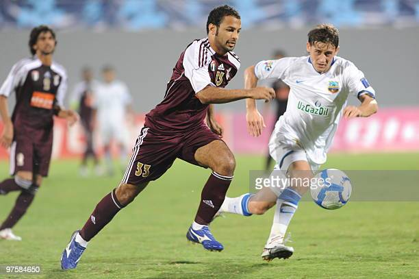 Emirati AlWahda club player Ahmad Ali Salem Khamis alAbri competes with an unidentified player of Uzbekistan's Bunyodkor club during their AFC...