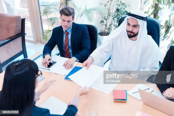 Emirati Arab Businessman handing an agreement to a businesswoman