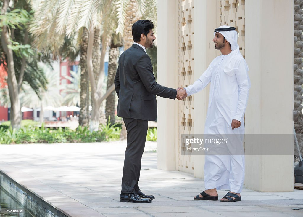 Emirati Arab man shaking hands with businessman outdoors