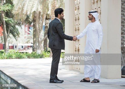 Emirati Arab man shaking hands with businessman outdoors