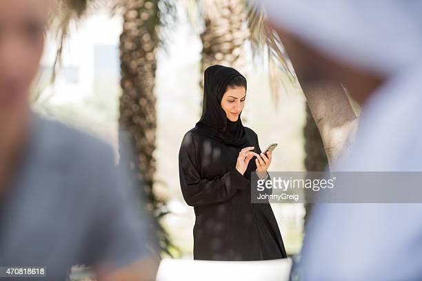 Emirati arab woman in black abaya using mobile smart phone